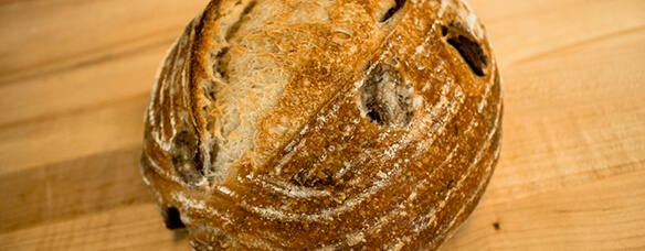 side photo of Kalamata olive bread has thin scrapes flecked by olives in crust